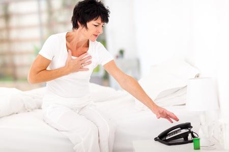 dolor de pecho: mujer de mediana edad que tiene un ataque al coraz�n y tratando de llegar a pedir ayuda por tel�fono Foto de archivo