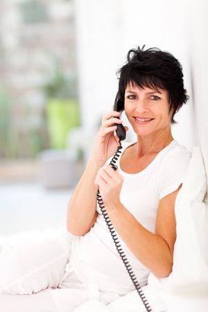 happy mid aged woman talking on landline phone photo