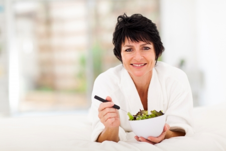 50s adult: beautiful mature woman lying on bed and eating green salad