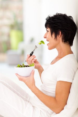 beautiful middle aged woman: beautiful middle aged woman eating salad at home