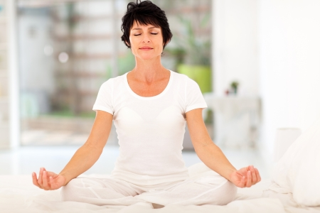 beautiful middle aged woman meditation on bed at home Stock Photo