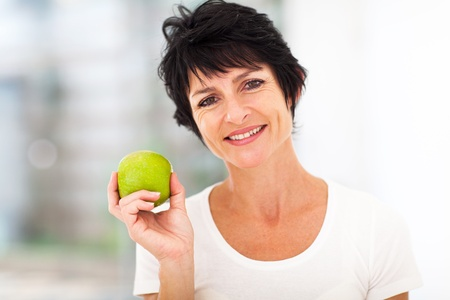 mid age: healthy mid age woman holding apple closeup