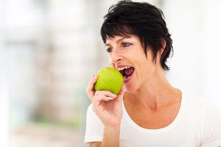 one adult: healthy middle aged woman eating a green apple Stock Photo