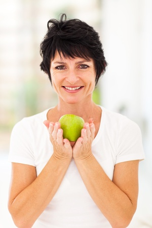 happy middle aged woman holding a green apple with both hands photo