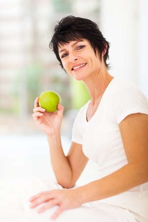 middle age women: beautiful mature woman holding a fresh green apple