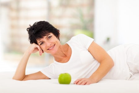 healthy person: attractive mature woman lying on bed with a green apple in front