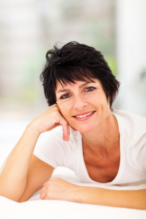 woman middle age: attractive middle aged woman lying on bed at home Stock Photo