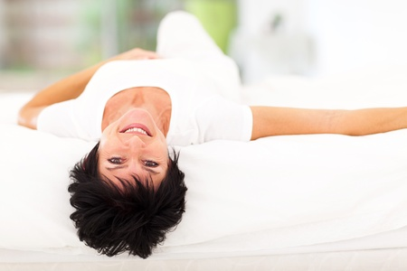 beautiful middle aged woman lying on bed at home photo