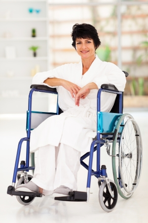 recovering: middle aged woman sitting on wheelchair recovering from injury
