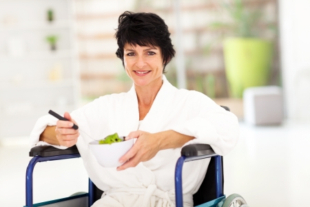 recovering: recovering middle aged woman eating salad on wheelchair