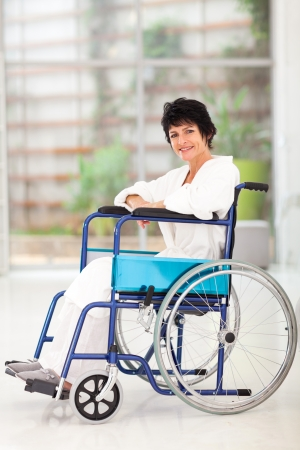 wheelchair woman: disabled middle aged woman sitting on wheelchair at home