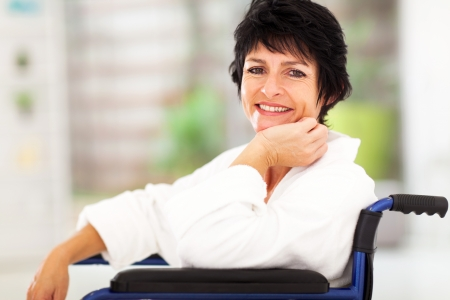 happy patient: happy middle aged woman sitting on wheelchair and recovering from sickness