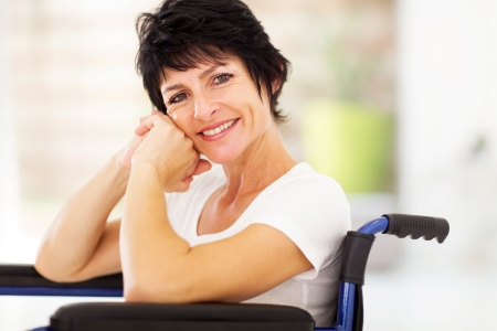 recovering: happy disabled middle aged woman sitting on wheelchair Stock Photo