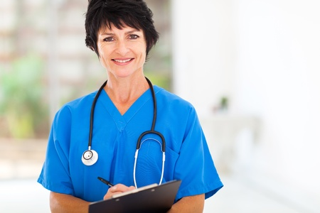 nurse clipboard: beautiful middle aged medical nurse in hospital office Stock Photo