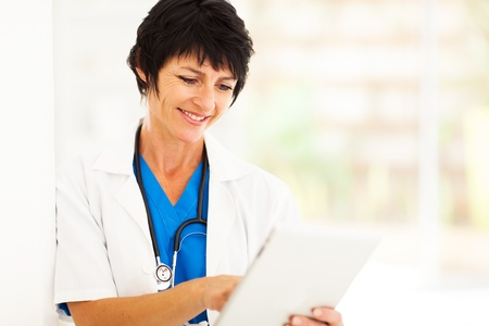 nurse computer: pretty female middle aged healthcare worker using tablet computer