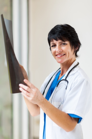 beautiful female middle aged doctor with x-ray in office photo