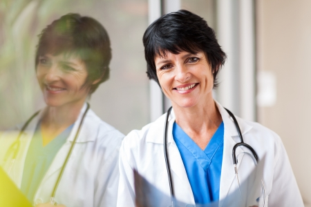 pretty female middle aged medical worker with x-ray standing by window photo