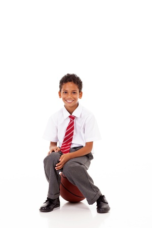 cute little primary schoolboy sitting on basket ball on white Stock Photo - 18075372