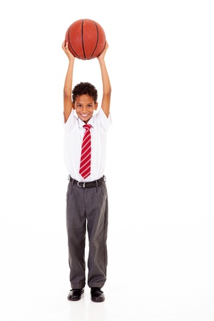 full uniform: little schoolboy holding a basket ball isolated on white