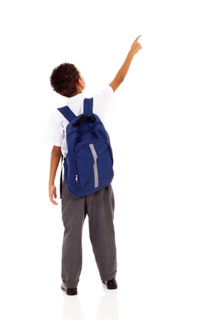 little schoolboy with schoolbag pointing at empty copy space Stock Photo - 18075394