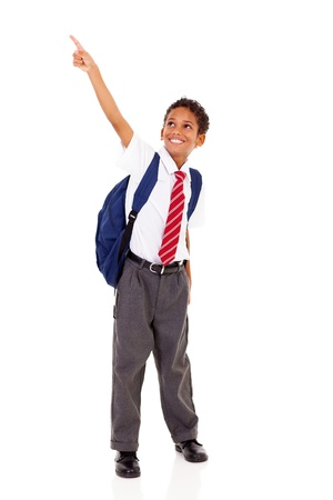 primary schoolboy pointing at empty copyspace isolated on white photo