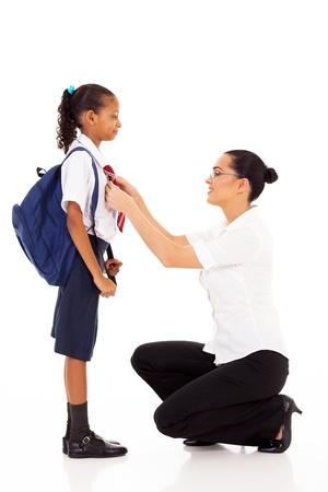 elementary school teacher helping schoolgirl fixing her tie