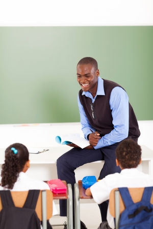 an elementary: male african primary school teacher teaching in classroom Stock Photo