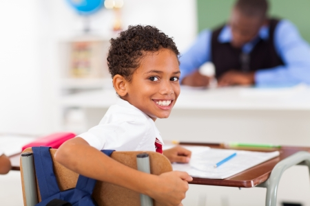 cute elementary schoolboy looking back in classroom photo