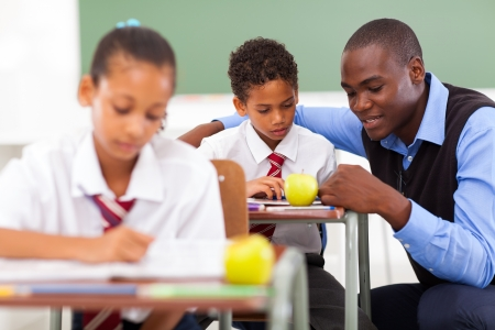 elementary school teacher helping student in classroom Stock Photo - 18075657