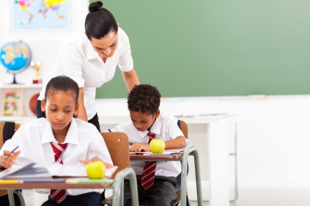 school children uniform: caring elementary school teacher and students in classroom Stock Photo