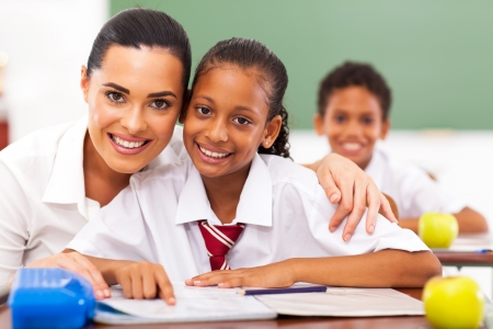 adults learning: pretty elementary school educator and students in classroom Stock Photo