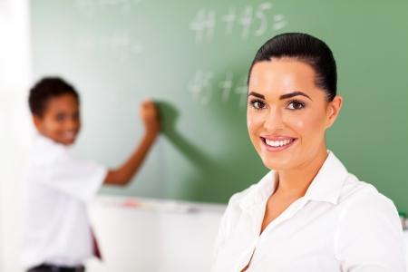 niños escribiendo: escuela bastante elemental profesor y el estudiante en frente de la pizarra Foto de archivo