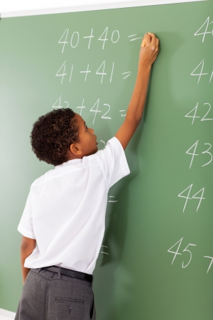 elementary school student writing maths answer on chalkboard Stock Photo - 18075659