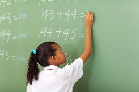 primary school girl writing maths answer on chalkboard photo