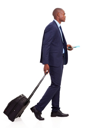 african american businessman walking with trolley bag on white photo