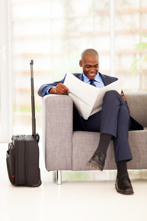 african businessman reading newspaper in airport vip lounge photo