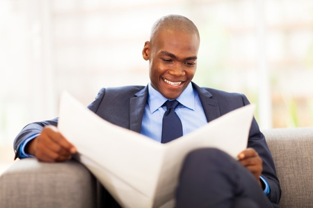 well read: handsome african corporate worker reading newspaper in office Stock Photo