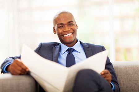 newspaper reading: african american businessman reading newspaper on sofa
