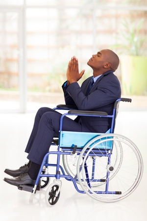 disabled african businessman sitting on wheelchair and praying photo