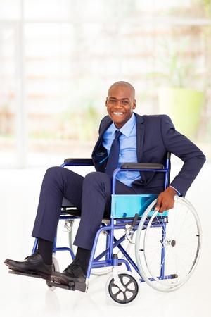 persona en silla de ruedas: optimista deshabilitado empresario afroamericano que se sienta en silla de ruedas