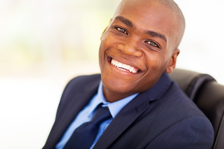 cheerful african american office worker sitting on office chair photo