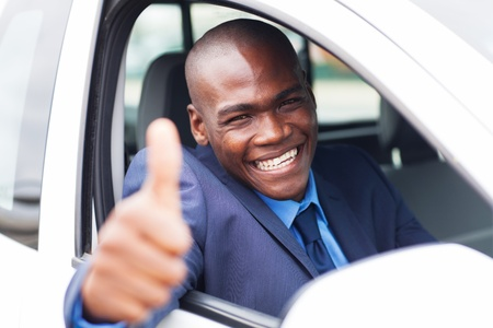 buying a car: happy african businessman giving thumb up inside new car Stock Photo
