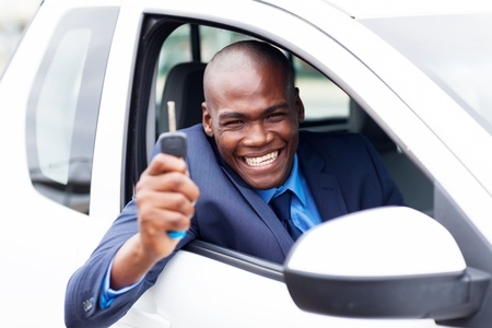 new motor vehicles: happy african vehicle buyer inside his new car with car key Stock Photo