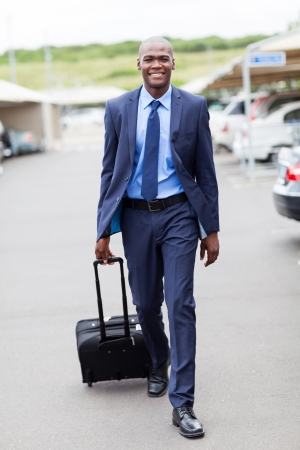 handsome african businessman walking in airport parking lot photo