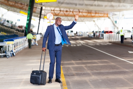luggage airport: african american businessman calling taxi in airport
