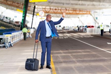 Afrikaanse Amerikaanse zakenman bellen taxi in luchthaven