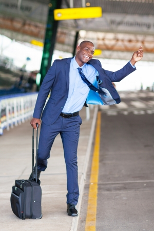 funny african american businessman calling taxi at airport photo