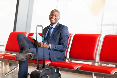 travel luggage: african american businessman waiting flight in airport