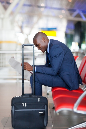 black businessman reading newspaper at airport photo