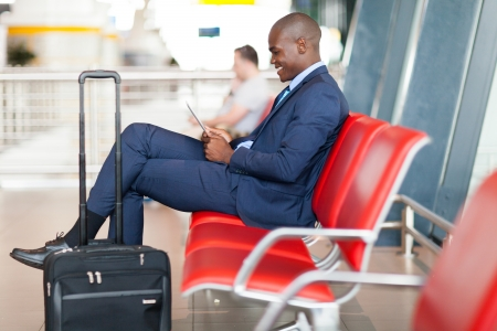 corporate travel: modern african businessman using tablet computer at airport